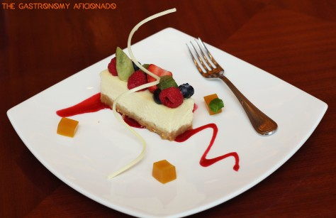 Cheesecake with graham cookies with mixed berries coulis