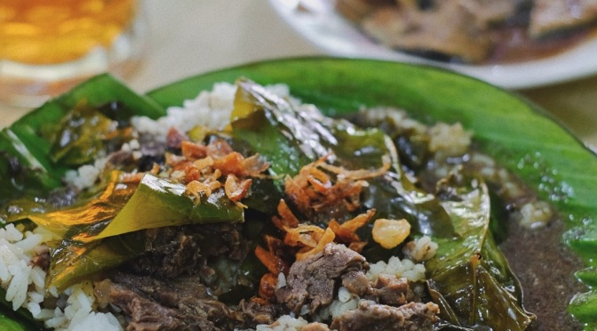 Sepiring nasi pindang kudus tersaji di atas piring beralaskan daun pisang.