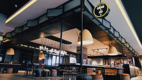 Sebuah cafe bernama Grab & Go dan sederetan tempat duduk serta meja.