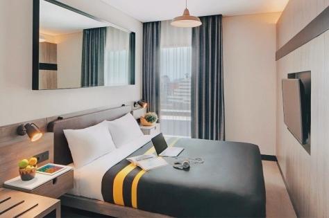 Sebuah kamar hotel dengan tempat tidur berukuran queen size dan TV.