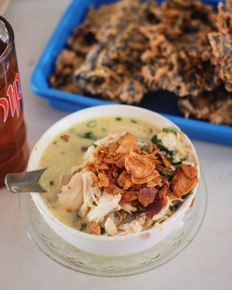 Semangkuk soto ayam kudus bersama minuman dan makanan pendamping.