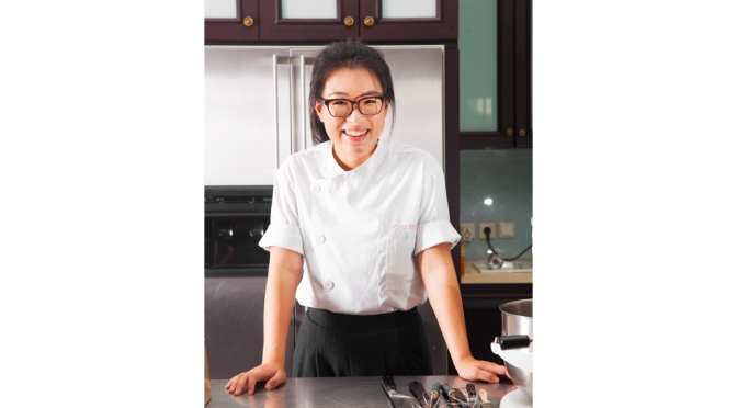 Chef Charins Chang is smiling behind a kitchen counter.
